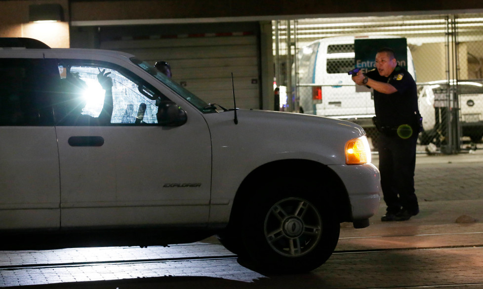 Dallas police stop a driver in downtown Dallas, Thursday, July 7, 2016, following shootings of police officers. Snipers apparently shot police officers during protests and some of the officers are dead, the city's police chief said in a statement. (AP Photo/LM Otero)
